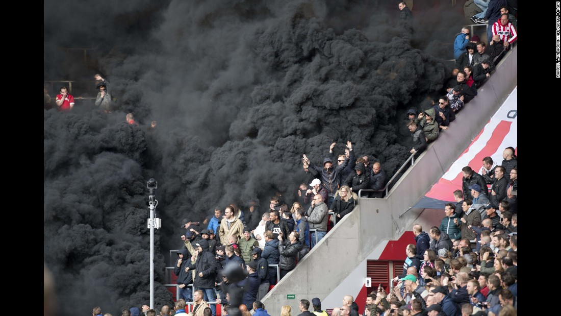 Black smoke engulfs part of the crowd after smoke bombs interrupted a soccer match in Eindhoven, Netherlands, on Sunday, April 23. A few fans had to receive medical treatment.