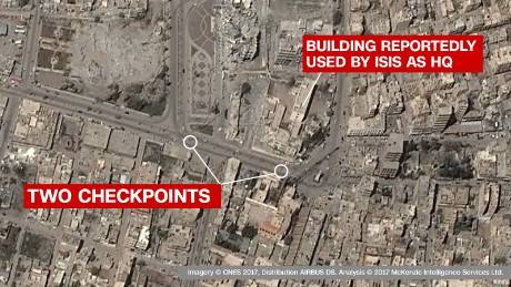 Checkpoints in front of reported ISIS HQ: The images clearly show two checkpoints in the main road outside a key governate building, which ISIS have reportedly used as a headquarters. The building itself is -- on the satellite imagery -- seen as damaged but still standing, suggesting a precision coalition airstrike.