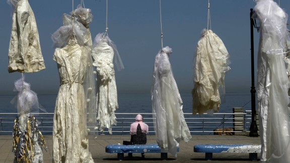 A woman sits on a bench near an installation of wedding dresses by Lebanese artist Mireille Honein and the NGO Abaad at Beirut Corniche on April 22, 2017, in tribute to the victims of the Lebanese penal code article 522.