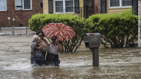 Nautica Jackson, left, and Aniya Ruffin walk through floodwaters with their dog as water threatened to enter their home in Raleigh, North Carolina.