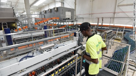 A worker oversees the bottle filling line at the Brassivoire beer factory in Abidjan.