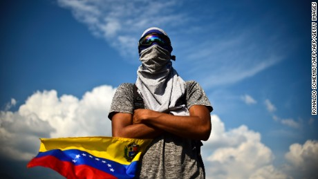 TOPSHOT - A Venezuelan opposition activist demonstrates against President Nicolas Maduro in Caracas, on April 24, 2017. Protesters rallied on Monday vowing to block Venezuela's main roads to raise pressure on Maduro after three weeks of deadly unrest that have left 21 people dead. Riot police fired rubber bullets and tear gas to break up one of the first rallies in eastern Caracas early Monday while other groups were gathering elsewhere, the opposition said.  / AFP PHOTO / RONALDO SCHEMIDT        (Photo credit should read RONALDO SCHEMIDT/AFP/Getty Images)