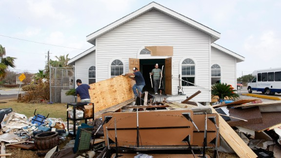 Workers remove debris on September 21, 2008, from Monte Calvario Pentecostal Church in Galveston, Texas, after it was damaged by a flood from Hurricane Ike.