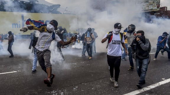 Opposition activists clash with riot police during a protest march in Caracas on April 26, 2017. Protesters in Venezuela plan a high-risk march against President Maduro Wednesday, sparking fears of fresh violence after demonstrations that have left 26 dead in the crisis-wracked country. / AFP PHOTO / JUAN BARRETO        (Photo credit should read JUAN BARRETO/AFP/Getty Images)