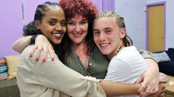 Ben Yosef (center) hugs two participants who have received Shanti House's services.