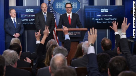 Reporters raise their hands with questions for Treasury Secretary Steven Mnuchin (R) and Chief Economic Advisor Gary Cohn (L) watched by White House Press Secretary Sean Spicer in the Brady Briefing Room on US President Donald Trump's tax reform plans on April 26, 2017 in Washington, DC.       (Photo credit should read MANDEL NGAN/AFP/Getty Images)
