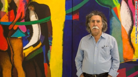 "Iraqi artist Dia Al-Azzawi poses for a picture with his work at the Arab Museum of Modern Art in the Qatari capital Doha, on October 19, 2016.  Azzawi, who is currently exhibiting his work in Doha, is pessimistic about the future of his country and sees ""scenario of destruction "" in the battle of Mosul. On October 17, 2016 Iraqi forces launched an operation to retake Mosul from the Islamic State (IS) group jihadists.  / AFP / OLYA MORVAN / RESTRICTED TO EDITORIAL USE - MANDATORY MENTION OF THE ARTIST UPON PUBLICATION - TO ILLUSTRATE THE EVENT AS SPECIFIED IN THE CAPTION        (Photo credit should read OLYA MORVAN/AFP/Getty Images)"