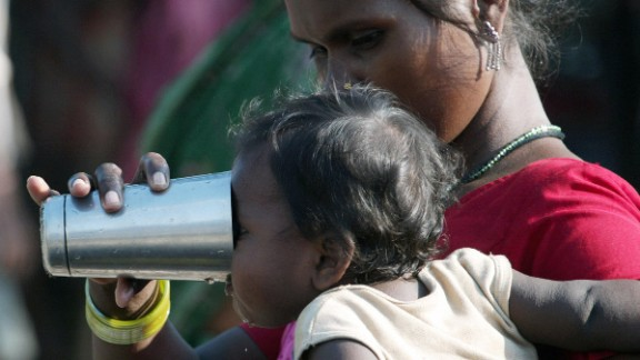 An Indian flood-affected villager gives drinking water to her child at a makeshift camp in the Purnia district of Bihar.