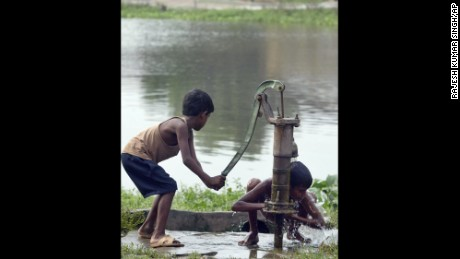 A flood-affected boy pumps water for another to bathe at a village in the northern Indian state of Bihar.