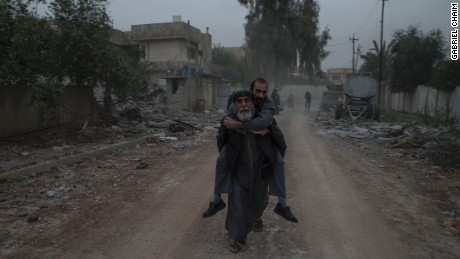 A man carries a sick relative on his back as they flee from their home in west Mosul's al Yarmouk neighborhood on April 11.