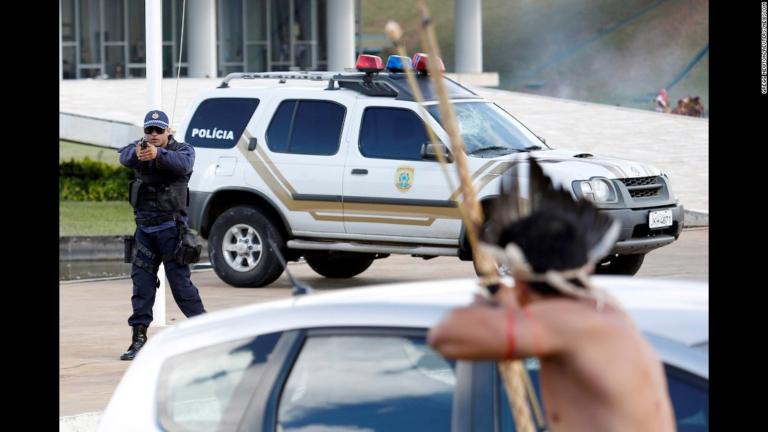 "A police officer points his gun at a man with a bow and arrow as indigenous groups held a demonstration in Brasilia, Brazil, on Tuesday, April 25. <a href=""http://www.reuters.com/article/us-brazil-protests-idUSKBN17R2ZH"" target=""_blank"">According to the Reuters news agency,</a> the indigenous groups were protesting farmers' encroachment on reservations."