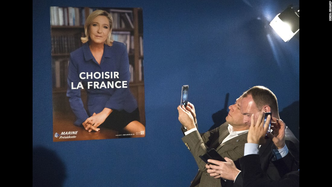 "Members of France's National Front party take photos of Marine Le Pen's new campaign poster on Wednesday, April 26. Le Pen, the leader of the far-right National Front, will face Emmanuel Macron in a presidential runoff next month. (""Choisir La France"" means ""Choose France."")"