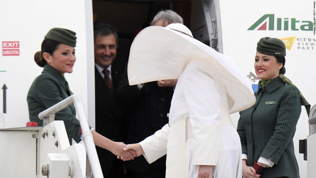 Francis shakes hands with Alitalia crew members before departing Rome on April 28.