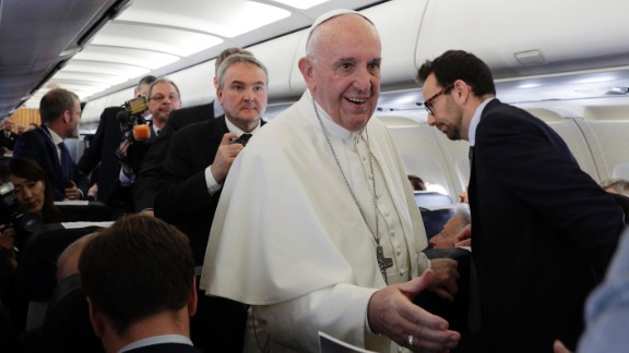 The Pope greets journalists on the airplane en route to Egypt.