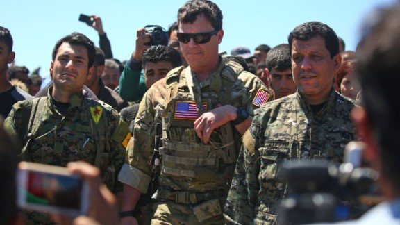 An officer from the US-led coalition stands alongside Kurdish fighters from the People