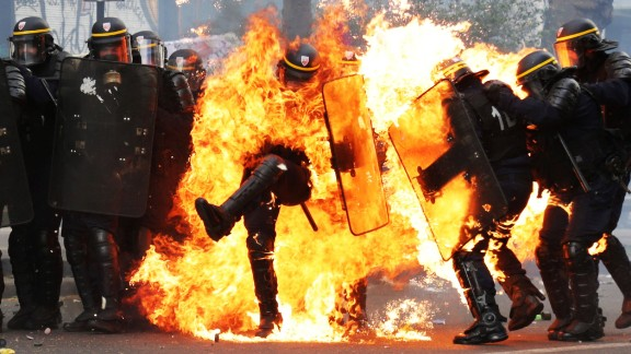 Police officers in Paris are engulfed in flames as they clash with May Day protesters on Monday, May 1. May Day protests turned violent in several cities around the world.