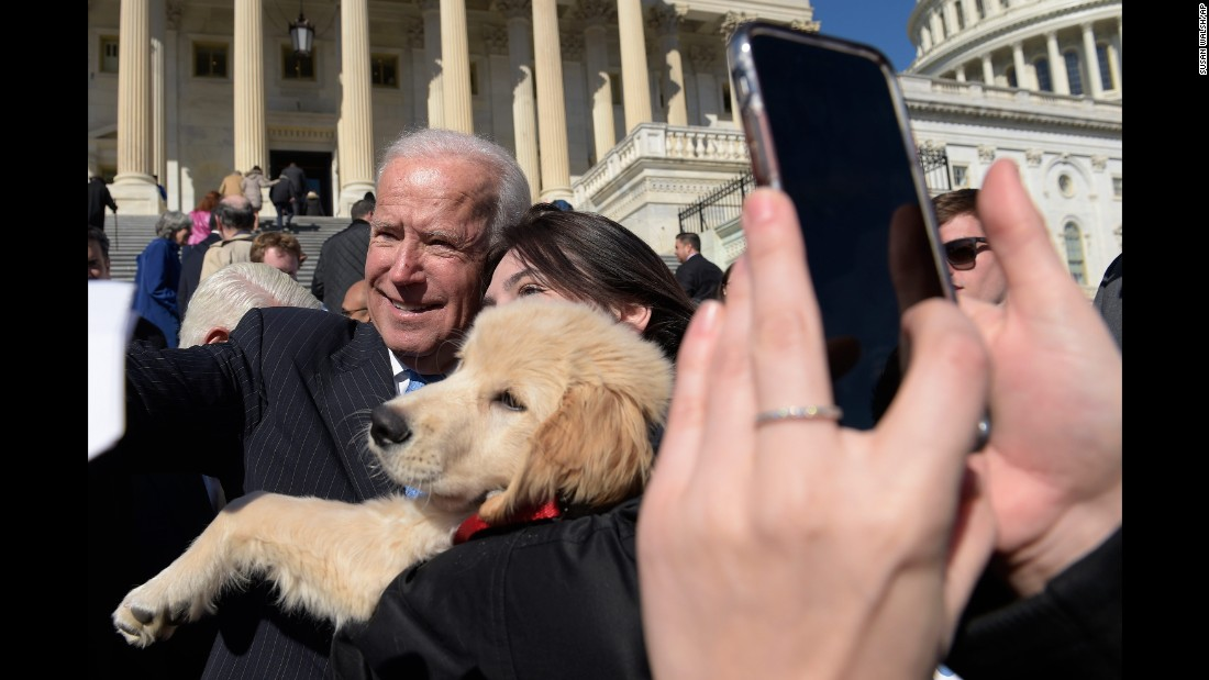 Biden poses for a photo with a dog named Biden as he greets a crowd on Capitol Hill in March.