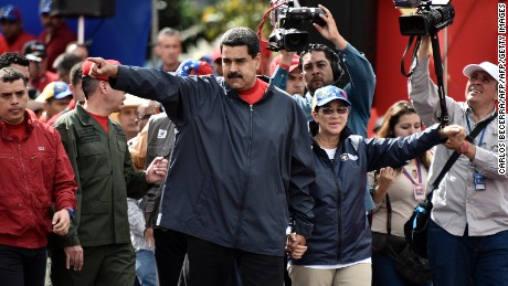 Venezuelan President Nicolas Maduro (L) and his wife Cilia Flores wave at supporters during a rally on May Day in Caracas, on May 1, 2017. Security forces in Venezuela fired tear gas to drive back protesters Monday as pro- and anti-government May Day rallies erupted exactly one month into a wave of deadly political unrest. Officers clashed with some 300 protesters, some throwing stones, who tried to break through security barriers to the electoral council headquarters in central Caracas.  / AFP PHOTO / Carlos BECERRA        (Photo credit should read CARLOS BECERRA/AFP/Getty Images)