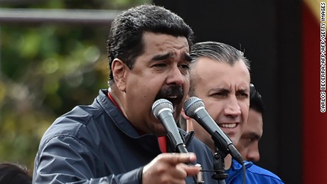 Venezuelan President Nicolas Maduro (L) delivers a speech next to Vice-President Tareck El Aissami during a rally on May Day in Caracas, on May 1, 2017. Security forces in Venezuela fired tear gas to drive back protesters Monday as pro- and anti-government May Day rallies erupted exactly one month into a wave of deadly political unrest. Officers clashed with some 300 protesters, some throwing stones, who tried to break through security barriers to the electoral council headquarters in central Caracas.  / AFP PHOTO / Carlos BECERRA        (Photo credit should read CARLOS BECERRA/AFP/Getty Images)