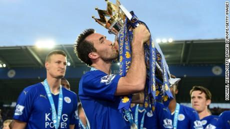 Christian Fuchs kisses the Premier League trophy.