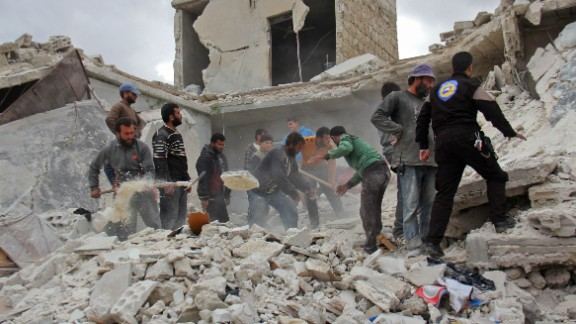 Rescuers and civilians view damage in a village on the outskirts of Idlib after November airstrikes.