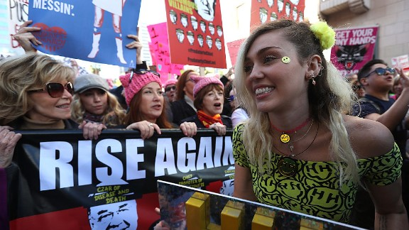 Singer Miley Cyrus (R) marches during the Women
