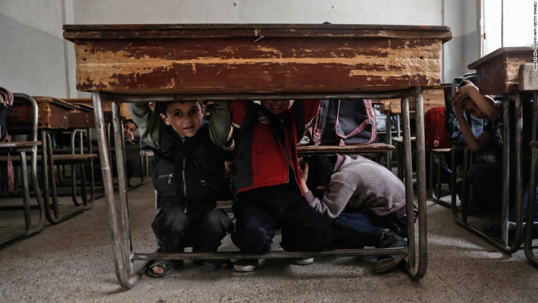Schoolchildren in Harasta, Syria, crouch under a desk during a safety awareness class on Tuesday, May 2. Syria's civil war is now in its seventh year.