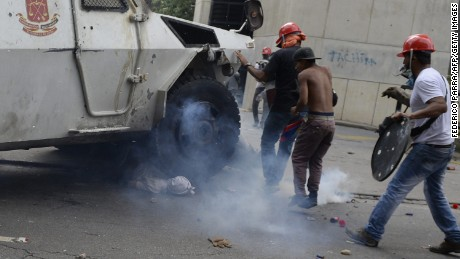 A Venezuelan National Guard riot control vehicle runs over an opposition demonstrator during a protest against Venezuelan President Nicolas Maduro, in Caracas on May 3, 2017. Venezuela's angry opposition rallied Wednesday vowing huge street protests against President Nicolas Maduro's plan to rewrite the constitution and accusing him of dodging elections to cling to power despite deadly unrest. / AFP PHOTO / FEDERICO PARRA / GRAPHIC CONTENT        (Photo credit should read FEDERICO PARRA/AFP/Getty Images)
