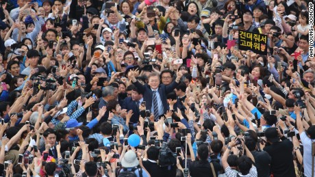 South Korea's presidential candidate Moon Jae-in, center raises his hands during a presidential election campaign in Goyang, South Korea.