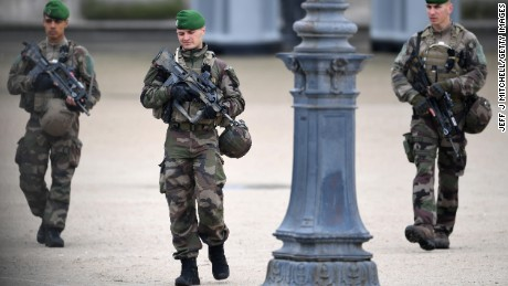 Soldiers patrol the Louvre in Paris, where Emmanuel Macron will hold a rally after polls close Sunday.