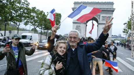 A man, flanked by a young woman, waves a French national flag next to people gesturing and shouting on the French avenue of the Champs Elysees.