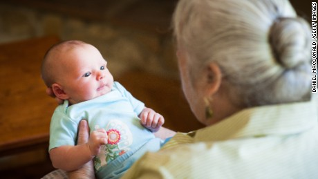 A grandmother holds her newborn granddaughter in her arms for the first time.  The infant is two weeks old.