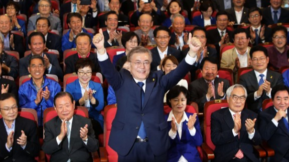 South Korean presidential candidate Moon Jae-in of the Democratic Party of Korea reacts after a television report on an exit poll of the new president at the party