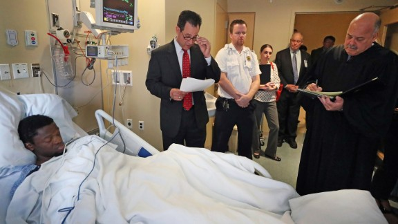 Bampumim Teixeira is arraigned from his hospital bed at Tufts Medical Center in Boston on Monday.
