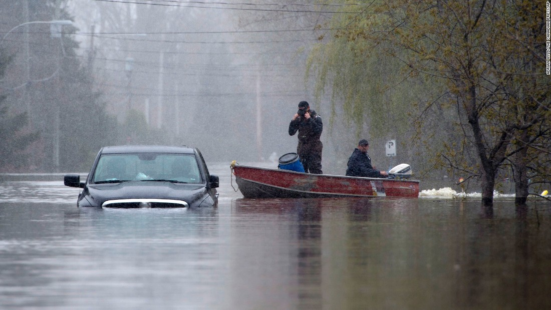 Two men pass a submerged truck in Gatineau, Quebec, on May 8.