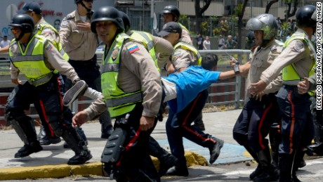 Police carry a demonstrator under arrest during a protest against President Nicolas Maduro's government in Caracas on April 4, 2017.  Activists clashed with police in Venezuela Tuesday as the opposition mobilized against moves to tighten President Nicolas Maduro's grip on power. Protesters hurled stones at riot police who fired tear gas as they blocked the demonstrators from advancing through central Caracas, where pro-government activists were also planning to march. / AFP PHOTO / FEDERICO PARRA        (Photo credit should read FEDERICO PARRA/AFP/Getty Images)