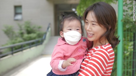 Yoon Ji-na with her 18-month-old daughter says she wants her country to return to normal.