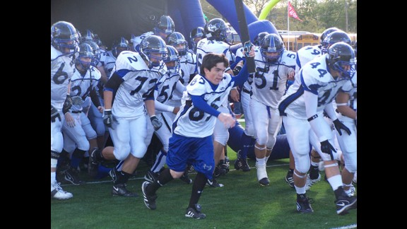 Ryan helps lead Hebron High School's football team to the field during its 2006 run to the Texas state championship. The coaches let Ryan play one snap his senior year.