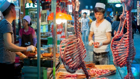 A Hui butcher carves lamb meat at the Muslim quarter in Xi'an. Much of the cuisine originates from central Asia and the Middle East.