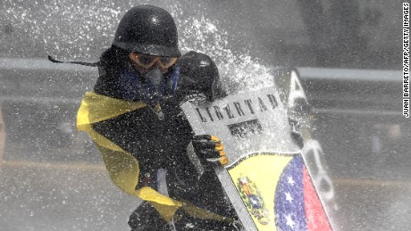 An oposition demonstrators is hit by the jet from a riot police water cannon during a protest against President Nicolas Maduro in Caracas, on May 10, 2017.