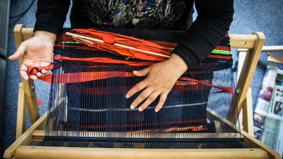 A weaver makes a welcome mat to sell for the Welcome Project, which raises money for female refugees