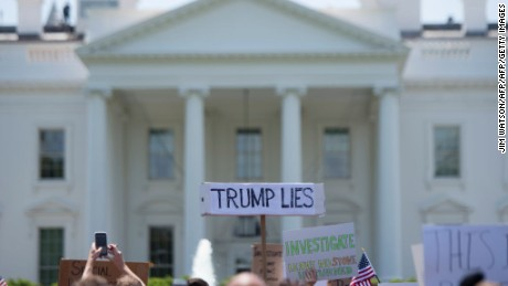 A protester holds a placard in front of the White House during a protest demanding an independent investigation in the Trump/Russia ties after the firing of FBI Director James Comey in Washington, DC, May 10, 2017.