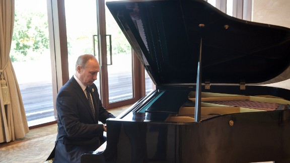 Russias President Vladimir Putin plays the grand piano ahead of a meeting with China's President Xi Jinping at the Diaoyutai State Guesthouse.