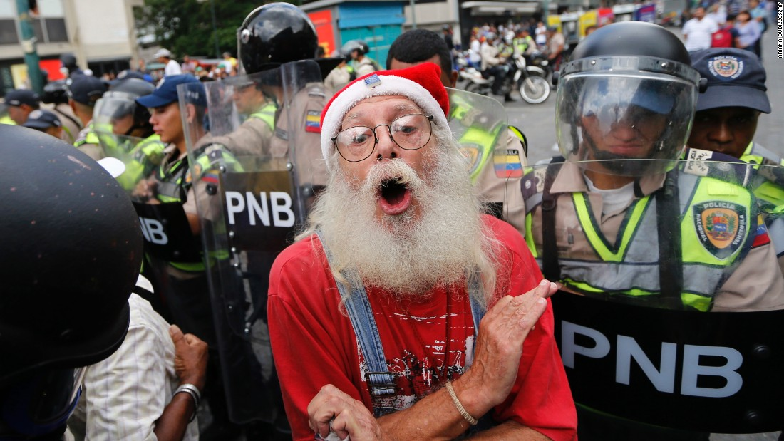 "During a <a href=""http://www.cnn.com/2017/05/12/americas/venezuela-grandparents-march/"" target=""_blank"">""Grandparents' March""</a> in Caracas, a man is blocked by police from reaching the Government Ombudsman's Office on Friday, May 12."