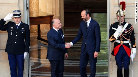 Newly appointed French Prime Minister Edouard Philippe, right, shakes hands with his predecessor, Bernard Cazeneuve, in Paris