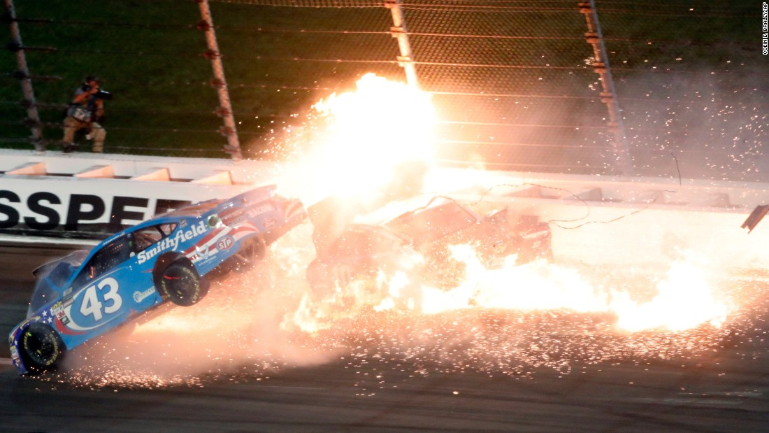 "The car of Aric Almirola (No. 43) <a href=""http://bleacherreport.com/articles/2709595-aric-almirola-out-of-hospital-suffered-fractured-vertebra-during-fiery-crash"" target=""_blank"">crashes into the car of Joey Logano</a> during the NASCAR Cup Series race at Kansas Speedway on Saturday, May 13. Almirola was airlifted to a hospital, where he was diagnosed with a fractured vertebra."