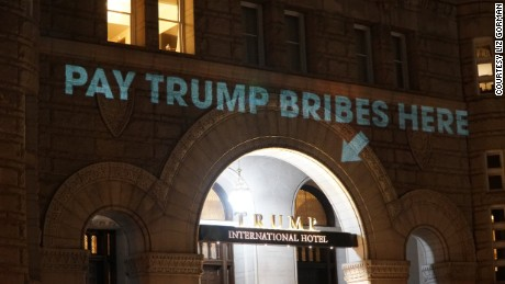 'Pay Trump bribes here' sign projected onto Trump's DC hotel