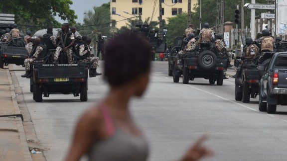 A woman walks past Ivorian soldiers patrolling by Ivory Coast
