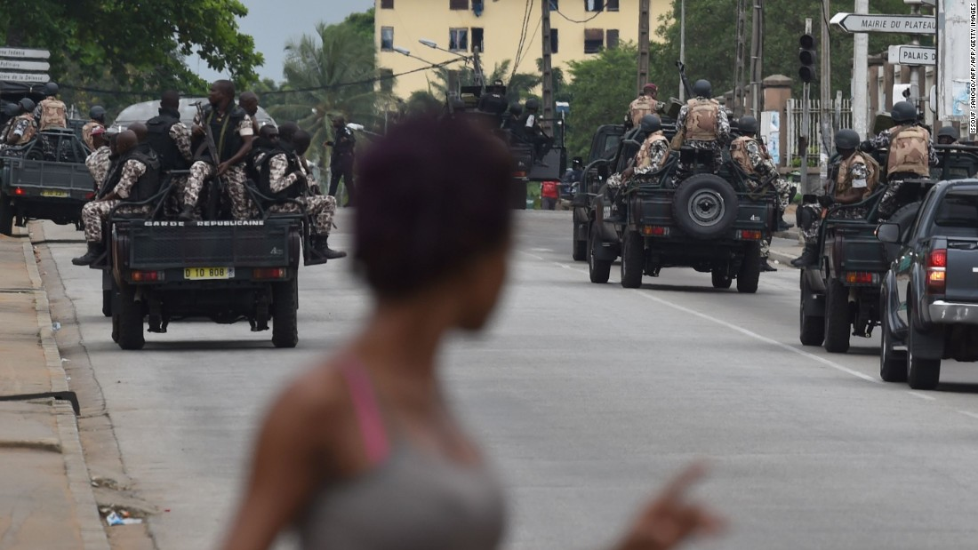 A woman walks past Ivorian soldiers patrolling by Ivory Coast's army headquarters, the Gallieni military camp, in Abidjan.<br />Banks, school and international institutions have closed during the uprising, leaving usually busy streets deserted.
