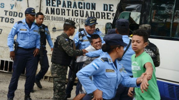 "Police hold a boy whose father was killed in 2016 by alleged gang members for refusing to pay them a ""war tax"" in Tegucigalpa, Honduras."